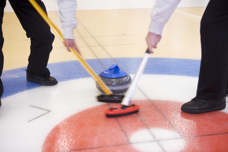 Curlers sweeping ahead of a rock. © Can Stock Photo Inc. / gemenacom