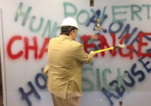 Downtown Mission CEO Ron Dunn takes a swing at a wall in their new facility to kick off construction and the new capital campaign, June 9, 2016. (Photo by Maureen Revait)
