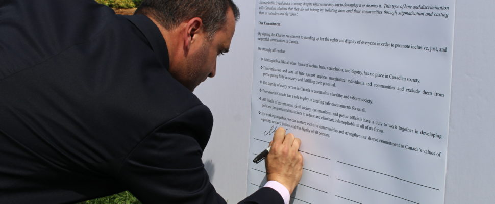 Executive Director of the National Council of Canadian Muslims Ihsaan Gardee signs the Charter for Inclusive Communities. (Photo by Mike Vlasveld)