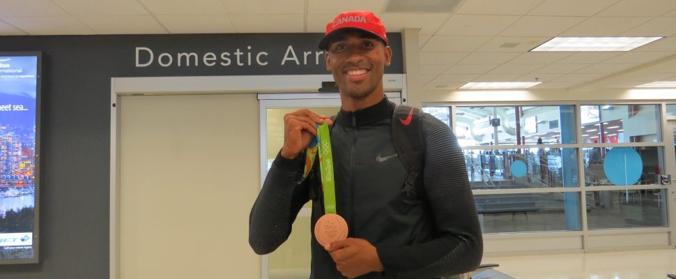 Damian Warner shows off his Olympic bronze medal upon his arrival back from Rio at the London International Airport, August 24, 2016. (Photo by Miranda Chant)