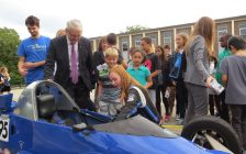 Waterloo-based racer Amy Castell shows Federal Transport Minister Marc Garneau, Grade 4 student Valeria Campos, and Grade 5 student Malachy Elliott her race car at Arthur Ford PS in London, September 14, 2016. (Photo by Miranda Chant, Blackburn News.)