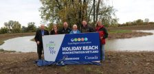 Ed Sleiman, Tracey Ramsey, Ian McRobbie, Claire Wales, Taras Natyshak and Annette Zahaluk unveil the sign for the Holiday Beach Demonstration Wetland. (Photo courtesy ERCA)