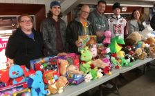 "Representatives from Blackburn Radio and the Chatham Goodfellows collect toys for the ""No Child Without a Christmas Campaign"" during the Chatham Maroons' annual Teddy Bear Toss game Sunday night. (Photo by Tom Heath)"