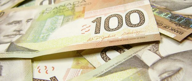 $100 bills in Canadian currency. Photo courtesy of © Can Stock Photo / devon.