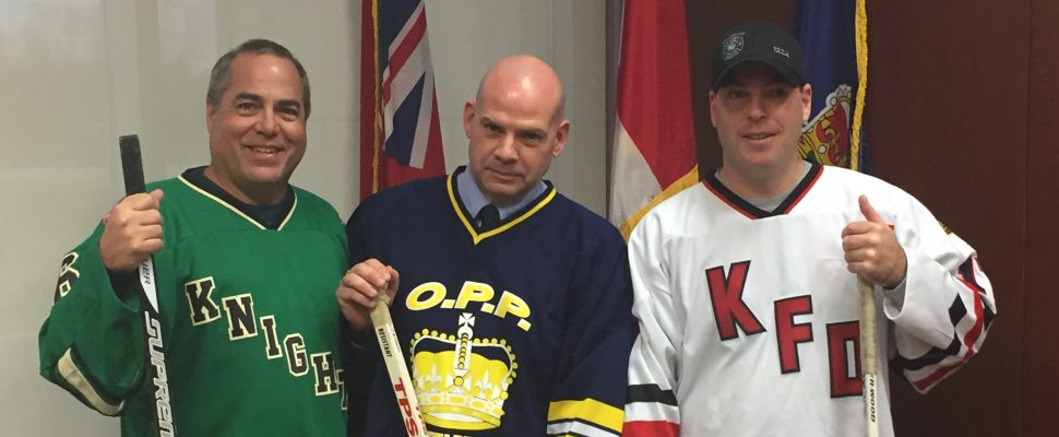 L-R: Peter Wolfe, KDSS Hockey Coach, Detective Constable Dave Hackney of South-Bruce OPP, and Mike Drake, acting captain for the Kincardine Fire Department, pose with hockey sticks at the unveiling for the Push For Change Hockey Challenge Kincardine event. January 19th, 2017. (Photo by Ryan Drury)