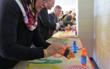 Diversity, Inclusion, and Anti-Oppression Advisory Committee Chair Rifat Hussain, Mayor Matt Brown, and Fanshawe College President Peter Devlin add their hand prints to a #HandsAgainstRacism banner, March 21, 2017. (Photo by Miranda Chant, Blackburn News.)