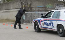 A London police forensics officer photographs evidence following a stabbing near Saunders Secondary School, March 9, 2017. (Photo by Miranda Chant, Blackburn News.)