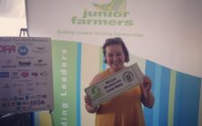Amanda Brodhagen  at the International Plowing Match & Rural Expo holding fundraiser custom gate sign.