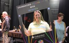"Shannon Paiva, Chatham-Kent tourism supervisor, posing with a ""Tourism Week"" photo sign at the brochure swap in the Chatham Capitol Theatre. May 30, 2017. (Photo courtesy of Sarah Cowan Blackburn News Chatham-Kent)."