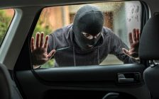 Man dressed in black looks through a car window wondering how to break in. (© Can Stock Photo / djedzura)