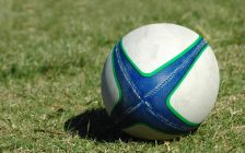 A white, green and blue Rugby ball lying on the lawn. (Photo courtesy of © Can Stock Photo / Ankevanwyk)
