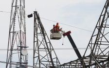 Two Hydro One employees work at the top of a transmission tower to pull new shield wire across the St. Clair River. (Photo submitted by Hydro One)