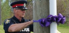 Sarnia Police Constable Chris Moxley places a purple ribbon at Indian Rd. and Exmouth St. May 17, 2016 (BlackburnNews.com Photo by Briana Carnegie)