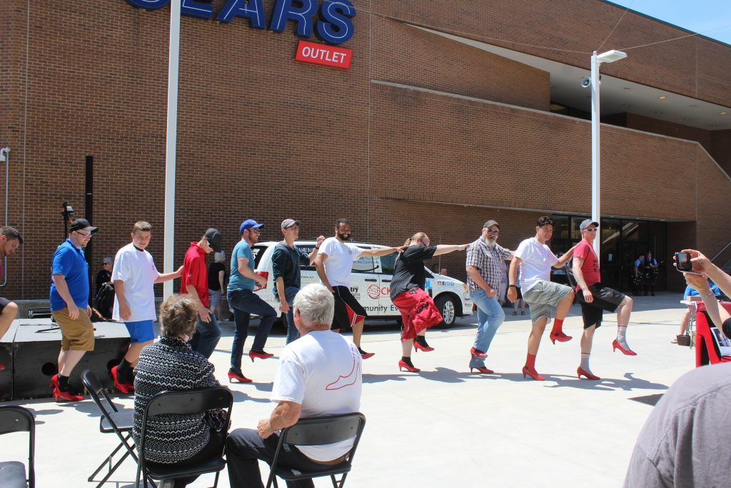 "Men dancing at ""Walk a Mile in Her Shoes"" event"