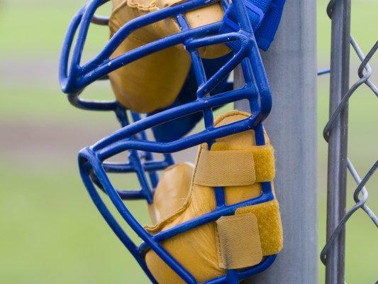 Umpires mask hanging on a backstop post. © Can Stock Photo / Joe_Photo