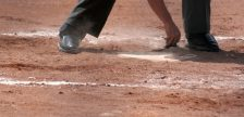 An umpire dusts off home plate.