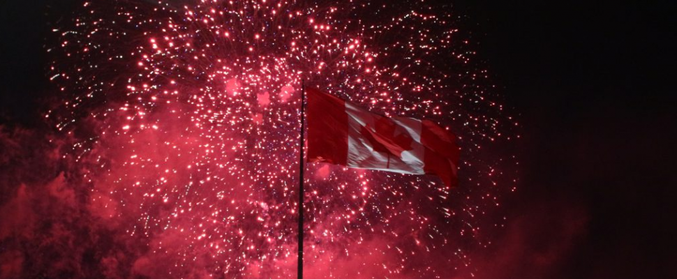 Fireworks light up the sky behind a Canadian flag. (Photo by Maureen Revait, Blackburn News)