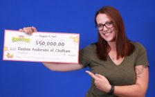 Justine Anderson holds up her Instant Crossword winnings. (Photo courtesy of OLG)