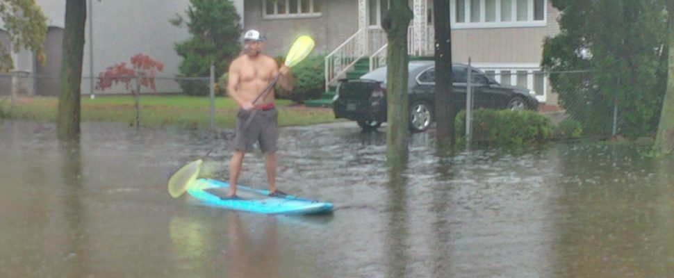 A man uses a paddle board to get around Glendale Ave. in east Windsor following widespread flooding, August 29, 2017. (Photo courtesy of Mike Hello)