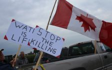WWF protesters hang upside down Canadian flag on Bush Line in Dover Centre. August 29, 2017. (Photo by Sarah Cowan Blackburn News Chatham-Kent).