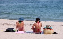 Two women sitting on the beach. Photo courtesy of © Can Stock Photo / Razvanjp.