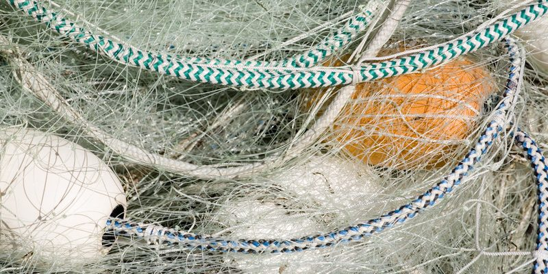 Photo of a fishing net with white floats. (Photo courtesy of © Can Stock Photo / thepoeticimage)