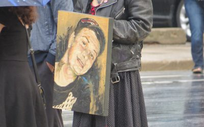 A painting of Adam Kargus is carried into the London courthouse by his sister, October 6, 2017. (Photo by Miranda Chant, Blackburn News)