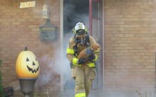 A firefighter rescues a dog from a simulated house fire in east London, October 10, 2017. (Photo by Miranda Chant, Blackburn News)