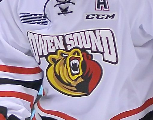 Close up of the front of a player wearing an Owen Sound Attack jersey.