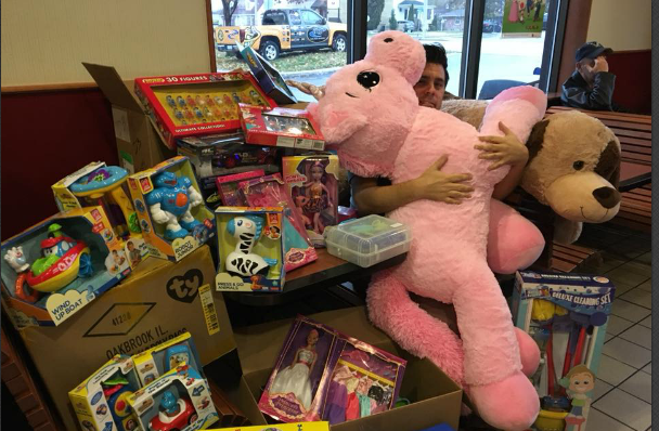 CHOK morning show host AJ Reynolds hugs a stuffed unicorn at the kick off for the annual Gift of Christmas toy drive. November 13, 2017 (BlackburnNews.com Photo.)