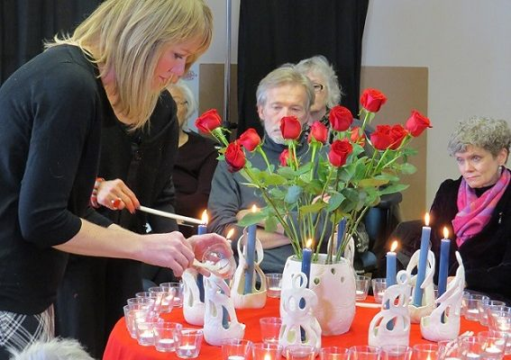 Kimberley Young-Milani of the Circle Women's Collective lights a candle in remembrance during a ceremony at My Sisters' Place that honours the victims of the Montreal Massacre. (Photo by Miranda Chant, Blackburn News)
