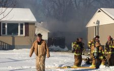 Homeowner Chris Biggs walks away from the scene as crews work to extinguish a fire that fully engulfed his garage on Minto St. January 9, 2018 (Photo by Melanie Irwin)