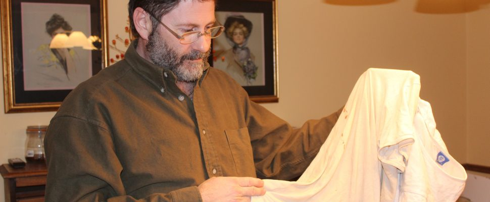 Sean Moore holding up blood-stained tee-shirt that he says he wore in a Syrian prison. February 10, 2018. (Photo by Sarah Cowan Blackburn News Chatham-Kent).