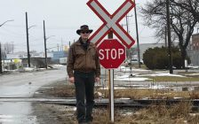 John Kinchsular stands by a new stop sign at Sarnia's St. Andrew St. rail crossing. February, 2018 (Photo submitted to BlackburnNews Sarnia)