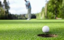 Golfer sinks a put. Ball about to go in the hole in the foreground. Golfer in the background.