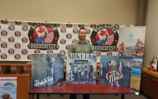 Bluewater Borderfest founder Mark Perrin stands behind posters of the three headliners for the musical festivals second annual event. May 10, 2018. (Photo by Colin Gowdy, BlackburnNews)