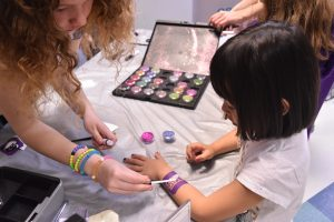 A St. John Vianney student receives her glitter tattoo. (Photo by Alyssa Leonard)