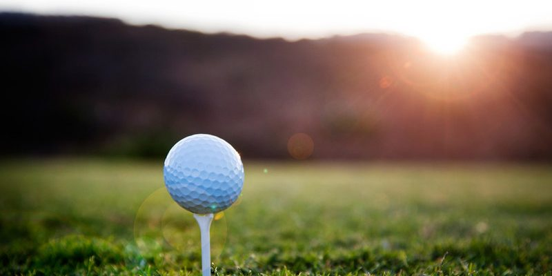Golf ball on a white tee, sunset in the back ground, selective focus.