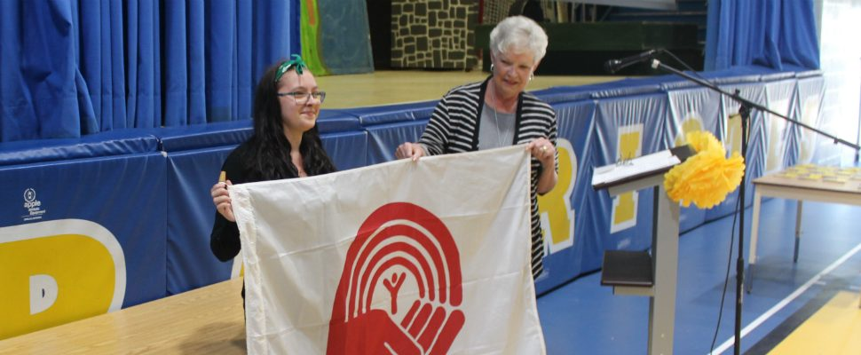 karen Kirkwood-White hold the United Way flag with new Chatham-Kent branch campaign chair Caterina Dawson at a ceremony at École secondaire catholique de Pain Court. June 15, 2018. (Photo by Greg Higgins)