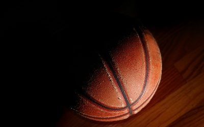 Old basketball closeup in dramatic light on the gym floor . © Can Stock Photo / zimmytws