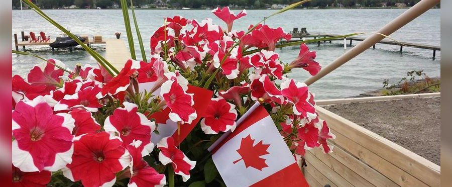A Canadian flag is seen among red and white flowers (Photo courtesy of Arlette Payne/Facebook)
