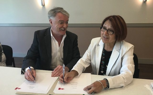 Sarnia Police Services Board Chair Mayor Mike Bradley and Aamjiwnaang Chief Joanne Rogers sign a new police agreement. July 10, 2018 (Photo by Melanie Irwin)
