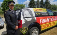 OPP Detective Superintendent Ken Leppert stands beside a minivan wrapped with information about the 1974 murder of Suzanne Miller, July 19, 2018. (Photo by Miranda Chant, Blackburn News)