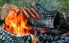 Hot dogs roasting over a campfire. © Can Stock Photo / who10