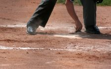 An umpire dusts off home plate. © Can Stock Photo / ca2hill