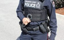 Police officer presenting handcuffs. (Photo by Greg Higgins)