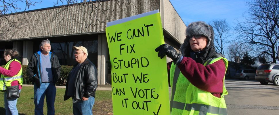 A protester at a Yellow Vest demonstration in Windsor holds a sign on January 5, 2019. (Photo by Adelle Loiselle)