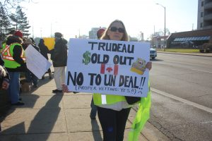 Dee Latta holds a sign at the Yellow Vest demonstration in Windsor on January 5, 2019. (Photo by Adelle Loiselle)