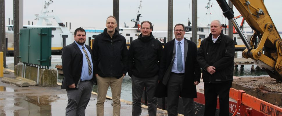 From left: Chatham-Kent councillor Anthony Ceccacci, Department of Fisheries and Oceans official Steve Newton, Senior Project Engineer Mike McDermott, Chatham-Kent Mayor Darrin Canniff, and Erieau Harbour Authority Corporation harbour manager Jeff Vidler pose for a photo at the Erieau Harbour. February 14, 2019. (Photo by Matt Weverink)
