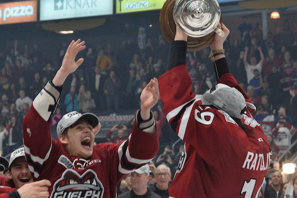 Guelph Storm Captain Isaac Ratcliffe holds the Robertson Cup over his head while teammates mob him on the ice.